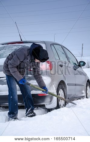 Man shoveling snow to free stuck car. Winter period.