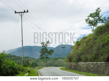 Landscape with road turn and green hills at summer.