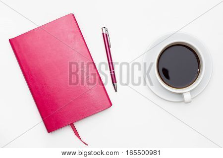 Cup of black coffee and diary with pen on white background. business minimal concept for women. Flat lay top view.