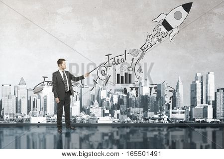 Man in abstract room with cityscape and rocket ship sketch. Start up concept