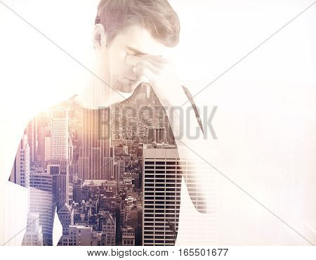 young businessman thinking against a city panorama. Mock up. Double exposure