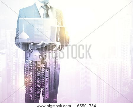 Businessman with laptop standing against a city panorama. Mock up. Double exposure