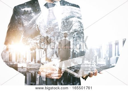 Thoughtful businessman with laptop on city and space background. Research concept. Double exposure.