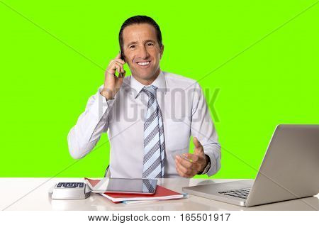 40 to 50 years old senior businessman working on computer laptop talking on mobile phone at office desk looking confident relaxed and successful isolated on green chroma key screen background