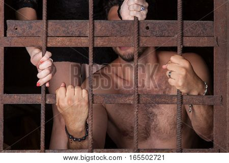 Man and woman holding on to the bars young couple enclosed in captivity