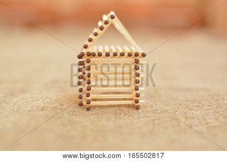 Wooden house made of matches. Handmade. Blurring background. Free place. Concept