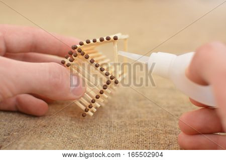 The Man Is Engaged In Manual Work Glue House With Matches. Handmade. Blurring Background. Free Place