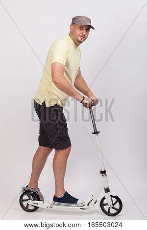 Young man riding a push scooter. Studio shot