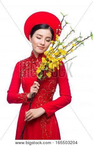 Portrait of a beautiful Asian woman on traditional festival costume Ao Dai holding Hoa Mai tree (Ochna Integerrima) flower. Tet holiday. Lunar New Year. poster