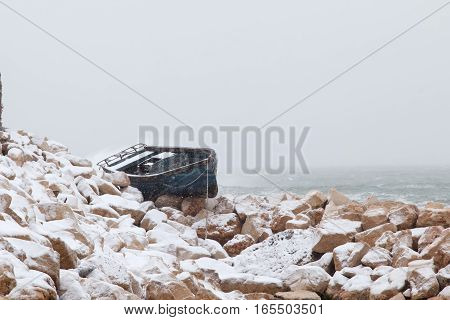 Fishing boat stranded on the shore after a winter storm