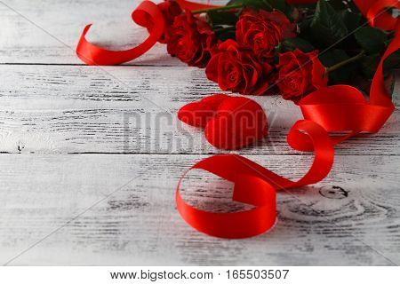 Bunch of red roses on table with ribbon
