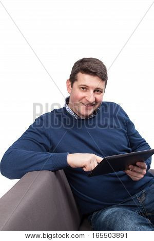 Confident young handsome man holding digital tablet and smiling while sitting on the couch. Isolated on white