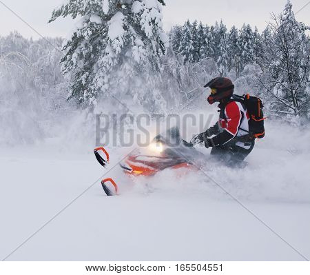 Athlete on a snowmobile moving in the winter forest in the mountains