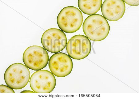 Backlit slices of different green zucchini thin slices, pattern for textured background. Abstract art composition of fresh organic vegetables