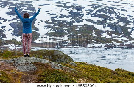 Travel freedom. Happy free tourist woman with arms raised outstretched up looking at landscape mountains covered with snow in Norway
