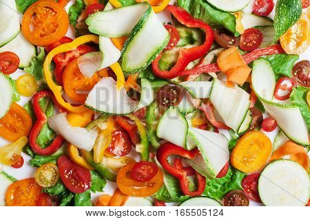 Mix of different red and yellow pepper and cucumber thin slices on white, pattern for textured background. Abstract art composition of fresh organic vegetables
