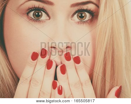 Expressions gestures concept. Portrait of shocked amazed attractive woman covering her mouth with hands showing red nails