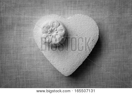 Heart and flowers made of paper mache on a fabric background to be used for crafts black and white