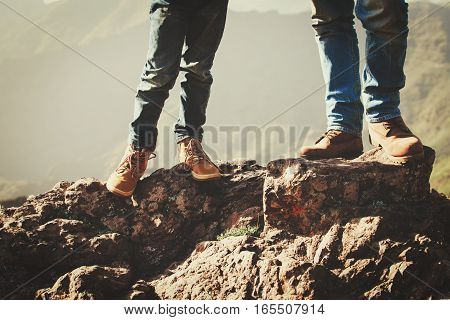 father and little son hiking boots in mountains