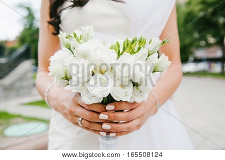 Bride holding bouquet white. Wedding flowers nature