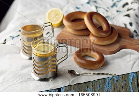 Mug of tea with lemon and bagels on a wooden background. Tea with lemon Baking bagels white tablecloth.