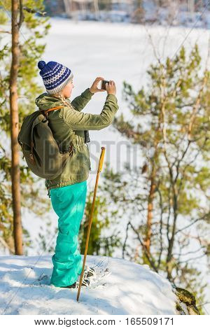 Young Beautiful Woman With Snowshoes And Mobile Phone Chill Out In The Forest