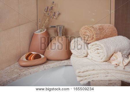 Stack of towels with a soap dispenser in a bathroom