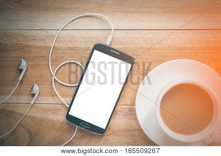Coffee cup and smatphone on wood background