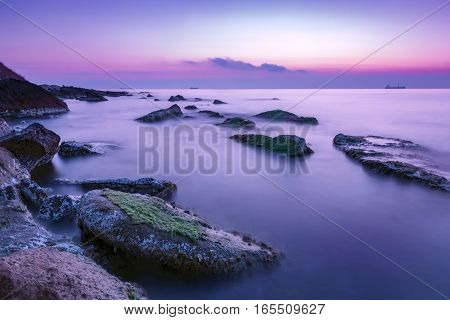 tranquility and calm long exposure rocky coast before sunrise .