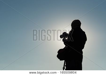 Silhouette of photographer taking photos. Filter effect style