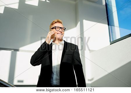 Businessman positive  blonde in a business suit, with glasses talking on phone, smiling. The sunlight  his face.