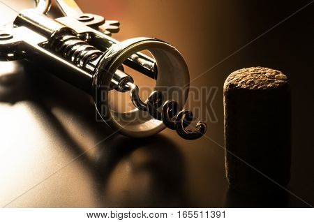 A corkscrew and cork sitting on a table.