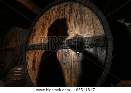 Shadow winemaker with a glass of wine on the background of a wine barrel