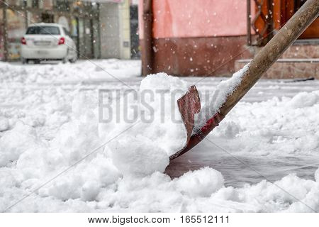 Cleaning snow with shovel in winter day from pavement