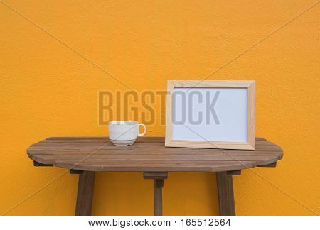 photo Frame and cup on a wooden on Yellow background .