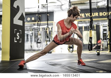 Wonderful smiling girl with closed eyes does stretching in the gym on the background of the hanging TRX straps. She wears a red sleeveless and sneakers, black shorts. Horizontal.