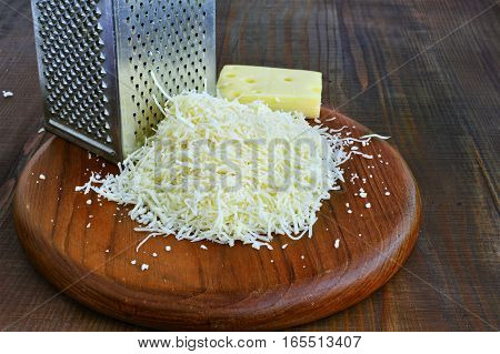 Emmental cheese and grater on wooden board