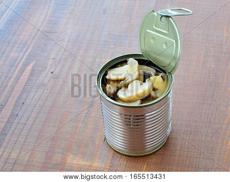 Canned button mushrooms in tin over wooden table