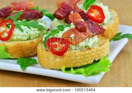 Canapes with herbed cream cheese bacon chilly and arugula on white plate
