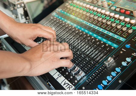 Hand adjusting volume fader of digital audio mixer. Professional sound engineer balancing volume of audio inputs. poster