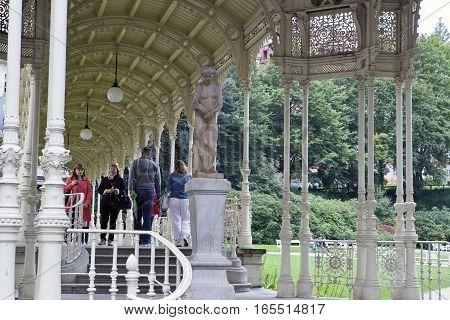KARLOVY VARY CZECH REPUBLIC - SEPTEMBER 14 2014: tourists walk along Sadova Colonnade(Garden colonnade) on September 14 2014 in Karlovy Vary Czech Republic