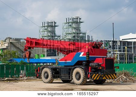 Mobile crane at condtruction site against powerplant construction background
