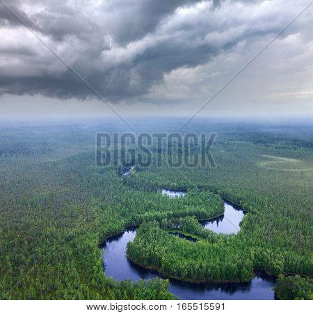 Aerial view above forest river during a flight in rainy summer day.