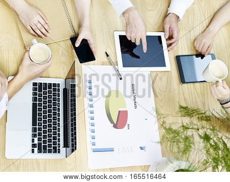 group of asian people meeting in office discussing business plan using tablet computer high angle view.