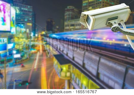 low angle shot on security camera with sky train in city background.