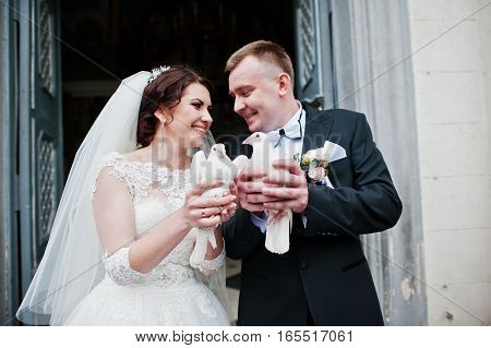 Happy Smiled Wedding Couple With Doves On Hands After Wedding Registration On Church.