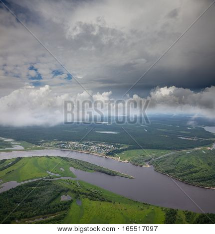 Small village on the bank of forest river in summer cloudy day aerial view