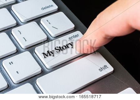 Finger on computer keyboard keys with My Story word