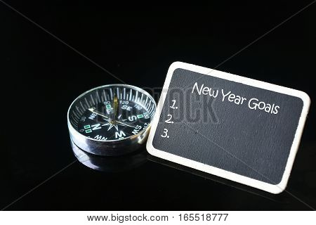 new year goals words on blackboard and compass