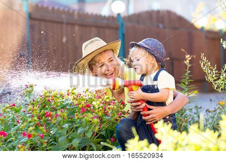 Happy mother and child watering in domestic garden
